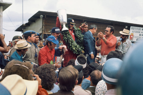 1974 Brazilian Grand Prix  Interlagos, Sao Paulo, Brazil. 25-27th January 1974.  Emerson Fittipaldi, McLaren, 1st position, celebrates on the podium with Clay Regazzoni, Ferrari, 2nd position, and Jacky Ickx, Lotus, 3rd position.  Ref: 74BRA04. World Copyright: LAT Photographic