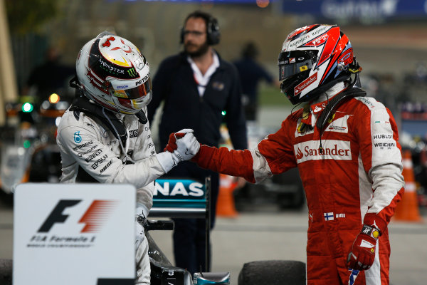 Bahrain International Circuit, Sakhir, Bahrain. Sunday 19 April 2015. Lewis Hamilton, Mercedes AMG, 1st Position, and Kimi Raikkonen, Ferrari, 2nd Position, congratulate each other in Parc Ferme. World Copyright: Sam Bloxham/LAT Photographic. ref: Digital Image _SBL9616