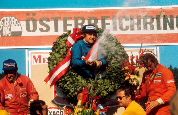 1974 Austrian Grand Prix.Osterreichring, Zeltweg, Austria.16-18 August 1974.Carlos Reutemann (Brabham Ford) 1st position, Denny Hulme (McLaren Ford) 2nd position and James Hunt (Hesketh Ford) 3rd position on the podium.Ref-74 AUT 02.World Copyright - LAT Photographic