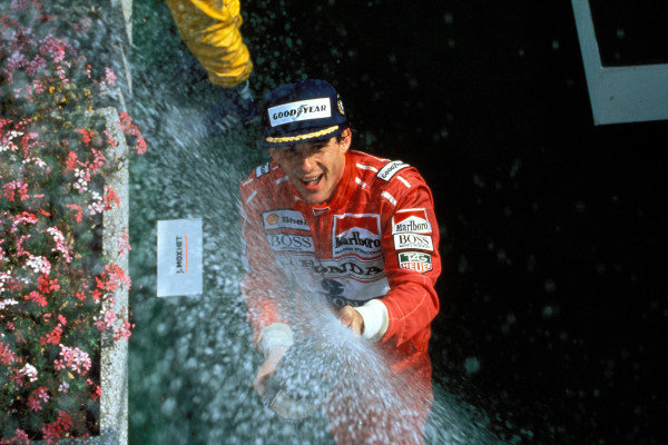 Ayrton Senna celebrates victory on the podium.