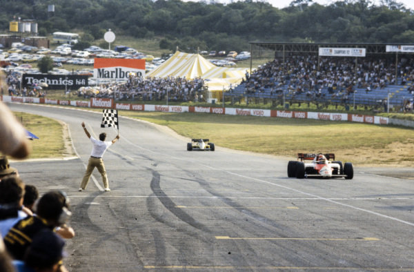 Niki Lauda, McLaren MP4-2 TAG, points to the sky as he takes the chequered flag to win the race. He leads Derek Warwick, Renault RE50.