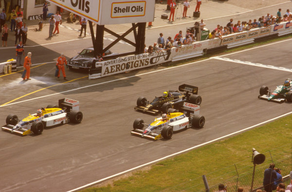 Brands Hatch, England.11-13 July 1986.Nelson Piquet leads away from Nigel Mansell (both Williams FW11 Honda's), Ayrton Senna (Lotus 98T Renault) and Gerhard Berger (Benetton B186 BMW) at the start.Ref-86 GB 26.World Copyright - LAT Photographic