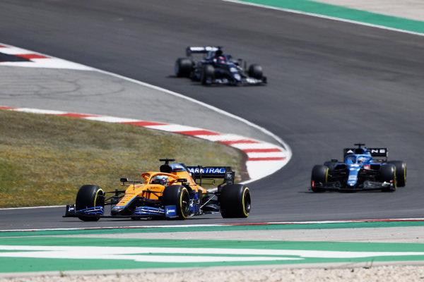Daniel Ricciardo, McLaren MCL35M, leads Fernando Alonso, Alpine A521, and Yuki Tsunoda, AlphaTauri AT02