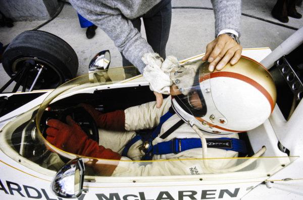 Mike Hailwood, McLaren M23 Ford, has his visor cleaned.