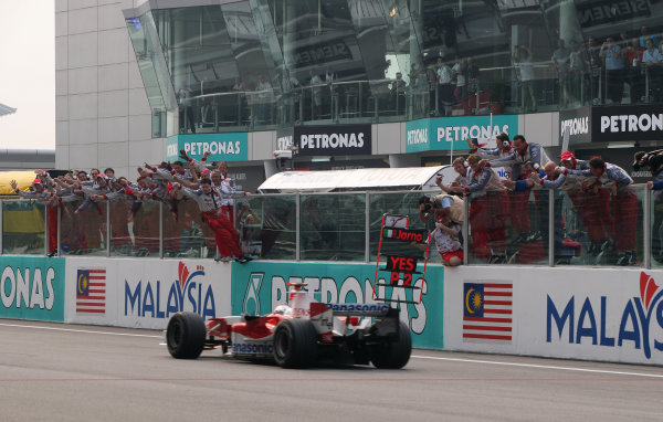 2005 Malaysian Grand Prix - Sunday Race, Sepang, Kuala Lumpur. Malaysia. 20th March 2005 2nd place finisher Jarno Trulli, Toyota TF105, crosses the finish line to the cheers of the Toyota team.World Copyright: Steve Etherington/LAT Photographic ref: 48mb Hi Res Digital Image Only