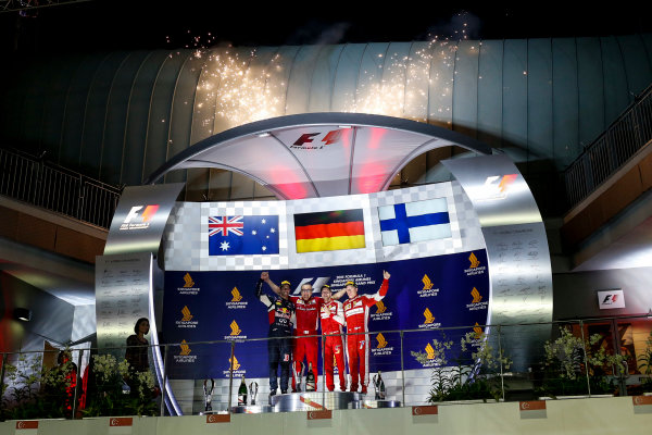 Marina Bay Circuit, Singapore. Sunday 20 September 2015. Daniel Ricciardo, Red Bull Racing, 2nd Position, Sebastian Vettel, Ferrari, 1st Position, Kimi Raikkonen, Ferrari, 3rd Position, pose for a photograph on the podium. World Copyright: Alastair Staley/LAT Photographic. ref: Digital Image _R6T7331