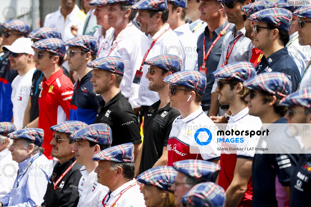 Drivers and team principals gather for a photo wearing flat caps in honour of the recent birthday of Sir Jackie Stewart, 3-time F1 Champion