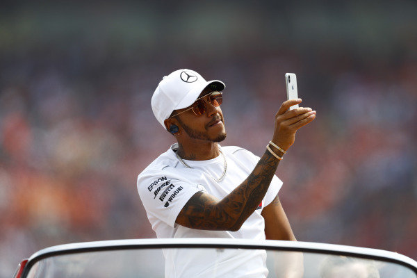 Lewis Hamilton, Mercedes AMG F1, uses his phone on the drivers' parade.