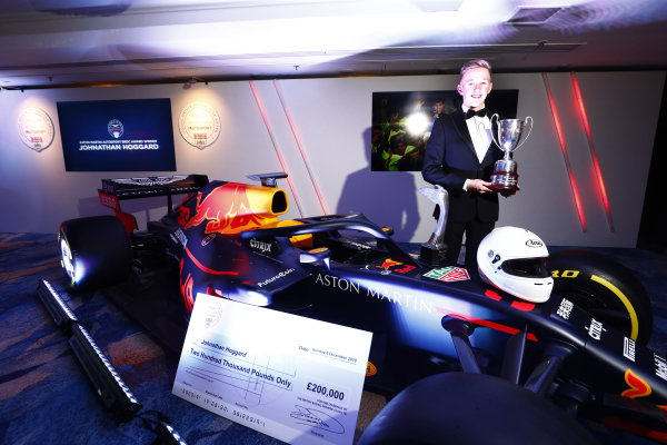 Aston Martin Autosport BRDC Young Driver Award winner Johnathan Hoggard with his trophy and cheque stands with the Red Bull Racing RB15