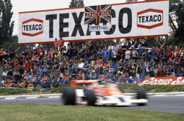 James Hunt passes a group of fans with flags of support in his McLaren M26 Ford.