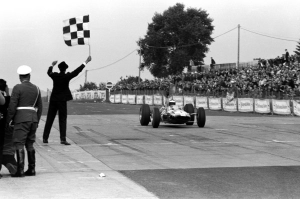 Jim Clark (GBR) Lotus 33 takes the chequered flag to secure his sixth victory of the season and his second World Championship crown. German Grand Prix, Nurburgring, 1 August 1965.
