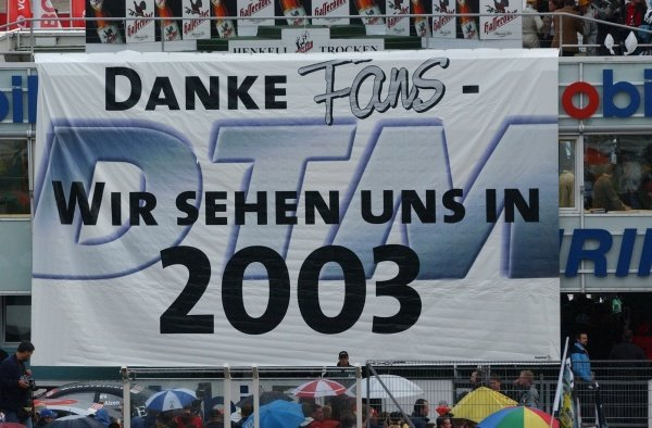 "DTM Championship 2002, Round 10 - Hockenheimring, Germany, 6 October 2002 - Drivers and teams thank the fans by unfolding a big banner with the message ""Thanks fans, we'll see each other again in 2003""."