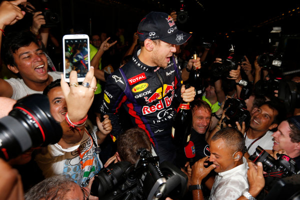Buddh International Circuit, New Delhi, India. Sunday 27th October 2013. Sebastian Vettel, Red Bull Racing, 1st position, celebrates with fans after securing fourth drivers world title. World Copyright: Charles Coates/LAT Photographic. ref: Digital Image _N7T5900