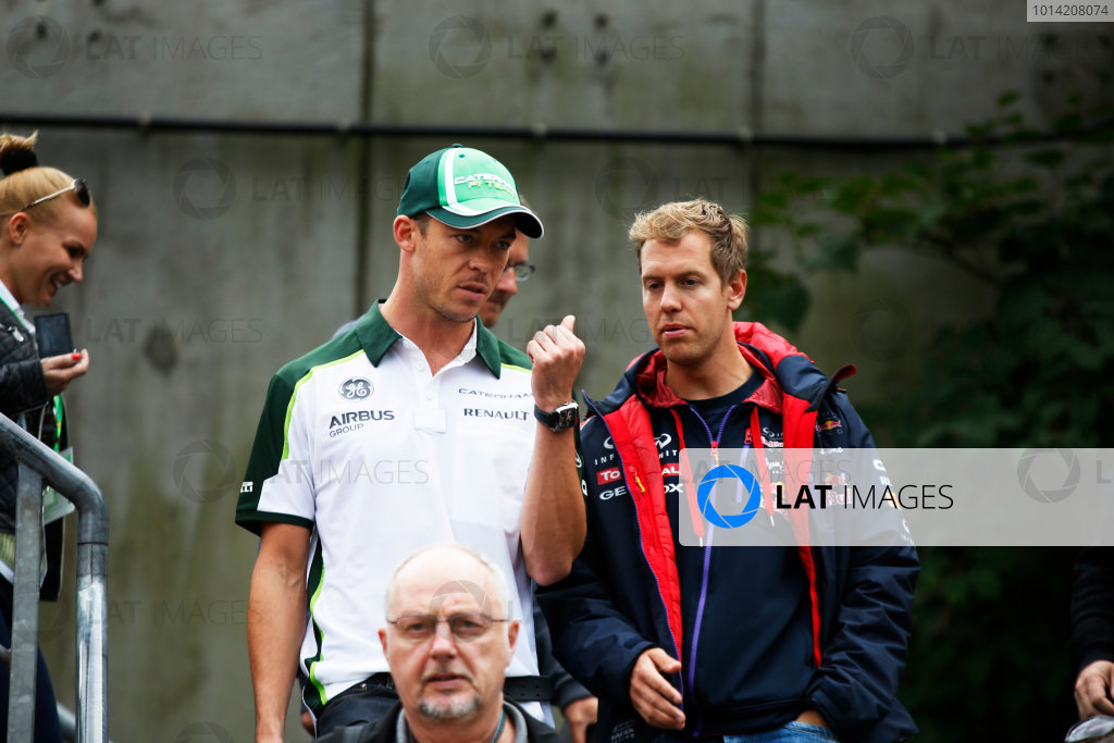 Spa-Francorchamps, Spa, Belgium. Friday 22 August 2014. Andre Lotterer, Caterham F1, and Sebastian Vettel, Red Bull Racing. World Copyright: Charles Coates/LAT Photographic. ref: Digital Image _J5R9254