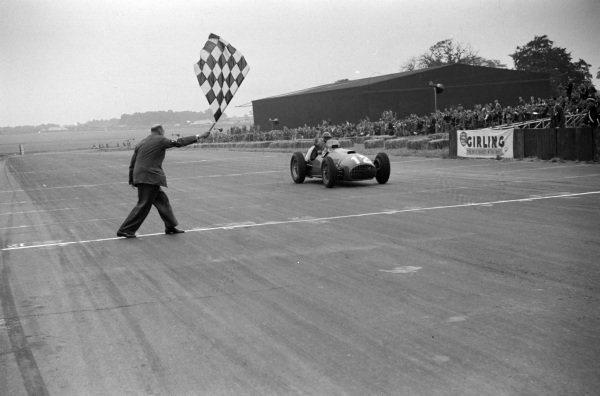 José Froilán González, Ferrari 375 takes the chequered flag for victory.