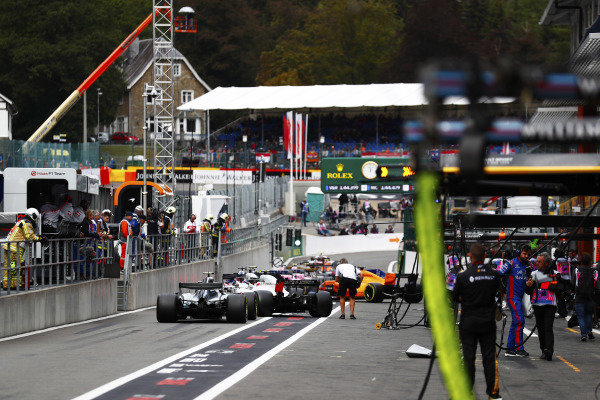 Valtteri Bottas, Mercedes AMG F1 W09, Kevin Magnussen, Haas F1 Team VF-18, Romain Grosjean, Haas F1 Team VF-18, and Brendon Hartley, Toro Rosso STR13, form the rear of a queue of cars in the pit lane, as FP3 is restarted following a red flag incident for a crash involving Stoffel Vandoorne, McLaren MCL33. Photographer Romano Poli can be seen on the right.
