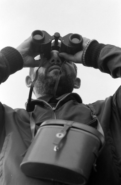Stirling Moss uses binoculars on the pit wall.