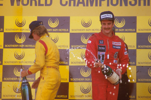 Kyalami, South Africa.17-19 October 1985.Nigel Mansell, 1st position and teammate Keke Rosberg, 2nd position (both Williams Honda) celebrate on the podium.Ref-85 SA 02.World Copyright - LAT Photographic