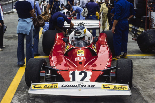 Mechanics work on the rear of Carlos Reutemann's Ferrari 312T2 while he sits in the cockpit.