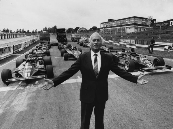 Brands Hatch, England.Colin Chapman, with a grid of Lotus F1 cars, portrait.World Copyright: LAT Photographic.Ref:  B/W Print.