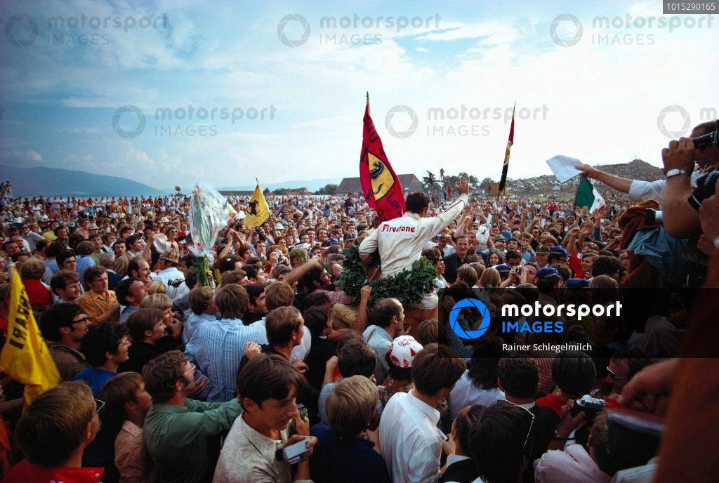 Jacky Ickx celebrates victory with a crowd of fans.