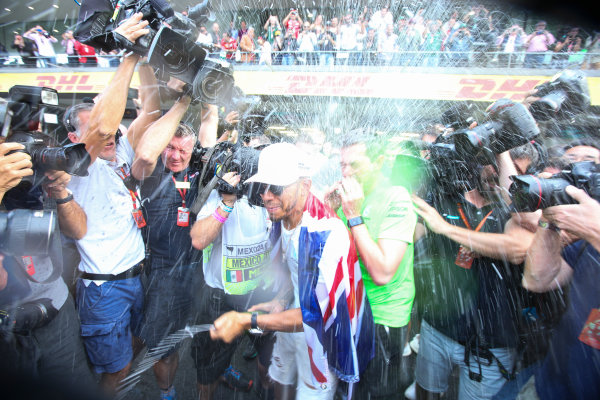 Autodromo Hermanos Rodriguez, Mexico City, Mexico. Sunday 29 October 2017. Lewis Hamilton, Mercedes AMG, sprays Champagne at photographers in celebration of securing his 4th world drivers championship title. World Copyright: Charles Coates/LAT Images  ref: Digital Image DJ5R7721