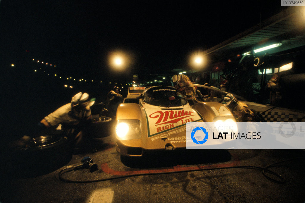 Daytona 24 Hours, Florida, USA. 30th - 31st January 1988. Rd 1. Al Holbert/Derek Bell/Chip Robinson (Porsche 962) takes a night time pit stop. 7th position, action. World Copyright: Bill Murenbeeld/LAT Photographic. Ref: 88IMSA DAY03