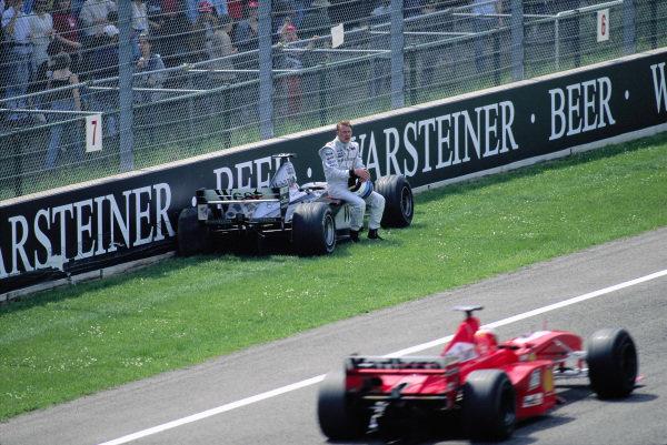 Mika Hakkinen, McLaren MP4-14, after crashing out of the race, is passed by Michael Schumacher, Ferrari F399.
