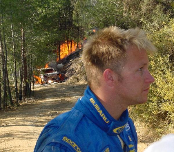 2001 Cyprus Rally.Petter Solberg keeps away from his burning Subaru.Photo:McKlein.