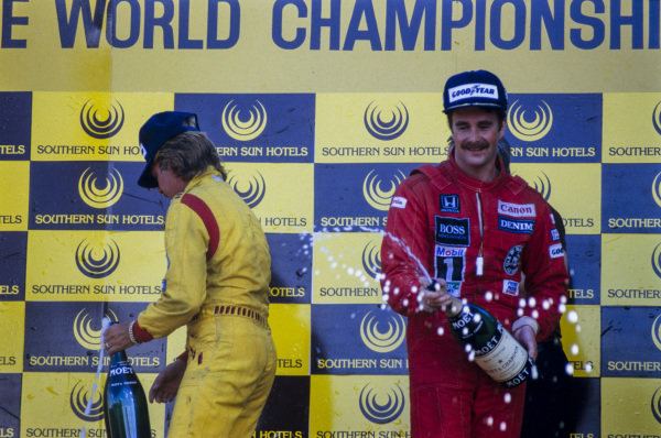 Nigel Mansell, 1st position, and teammate Keke Rosberg, 2nd position, celebrate on the podium.