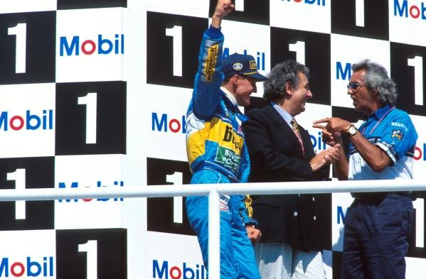 Opera singer, Placido Domingo, centre, joins Michael Schumacher and Flavio Briatore on the podium.