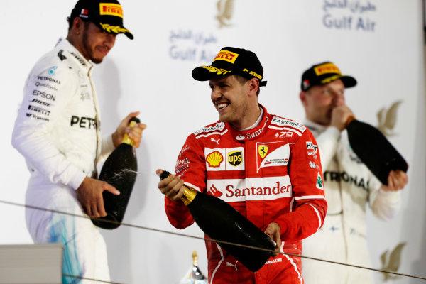 Bahrain International Circuit, Sakhir, Bahrain.  Sunday 16 April 2017. Sebastian Vettel, Ferrari, celebrates on the podium with Lewis Hamilton, Mercedes AMG, and Valtteri Bottas, Mercedes AMG. World Copyright: Charles Coates/LAT Images ref: Digital Image _27I0977