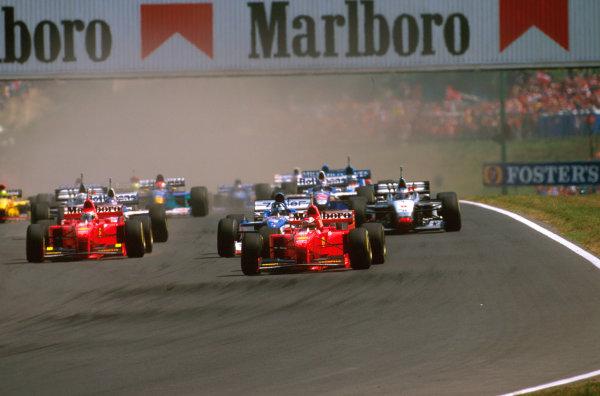 Hungaroring, Hungary.8-10 August 1997.Michael Schumacher (Ferrari F310B) heads down to the first corner at the start, closely followed by Damon Hill (Arrows A18 Yamaha) and Eddie Irvine (Ferrari F310B).Ref-97 HUN 24.World  Copyright - LAT Photographic