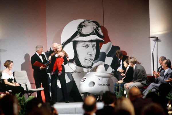 Grosvenor House Hotel, Park Lane, London. 6th December 1992.John Surtees receives his This Is Your Life red book from Michael Aspel on the stage at the Autosport Awards evening. He is carrying his son Henry.World Copyright: Gary Hawkins/LAT Photographic.Ref: 35mm Transparency Image