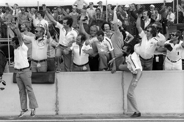 The Ligier team celebrate on the pit wall as Jacques Laffite (FRA) Ligier, wins his and the team's first GP.
