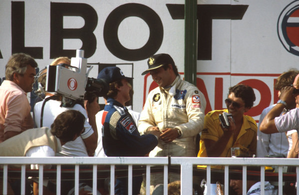 Osterreichring, Austria.13-15 August 1982.Elio de Angelis (Lotus Ford) 1st position is congratulated by Keke Rosberg (Williams Ford) 2nd position on the podium after their very close finish. Ref-82 AUT 03.World Copyright - LAT Photographic