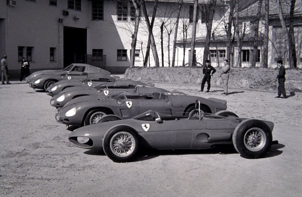 "A selection of racing Ferraris are displayed outside the Ferrari factory, including a Ferrari 156 ""Sharknose"".