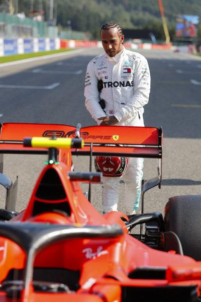 Lewis Hamilton, Mercedes AMG F1, inspects the Charles Leclerc Ferrari SF90