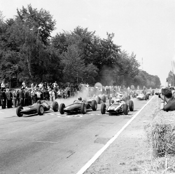 1962 French Grand Prix. Rouen-les-Essarts, France. 6-8 July 1962. Poleman Jim Clark (Lotus 25 Climax) smokes up his rears as he leads away from Graham Hill (BRM P57) and Bruce McLaren (Cooper T60 Climax) on the grid at the start.  Ref-14563. World Copyright - LAT Photographic