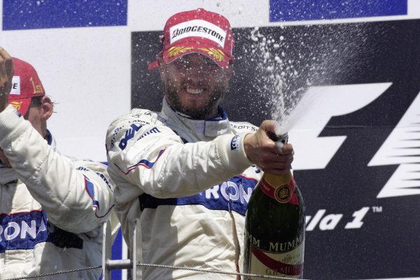 Nick Heidfeld sprays champagne on the podium.