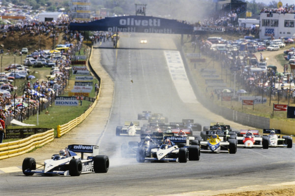 Nelson Piquet, Brabham BT54 BMW, locking up as he leads Marc Surer, Brabham BT54 BMW, Elio de Angelis, Lotus 97T Renault, Ayrton Senna, Lotus 97T Renault, Keke Rosberg, Williams FW10 Honda, Niki Lauda, McLaren MP4-2B TAG, and Alain Prost, McLaren MP4-2B TAG as he enters the first corner at the start.