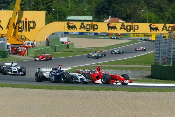 Race winner Michael Schumacher (GER) Ferrari F2004 and Juan Pablo Montoya (COL) Williams FW26 go side by side on lap one.