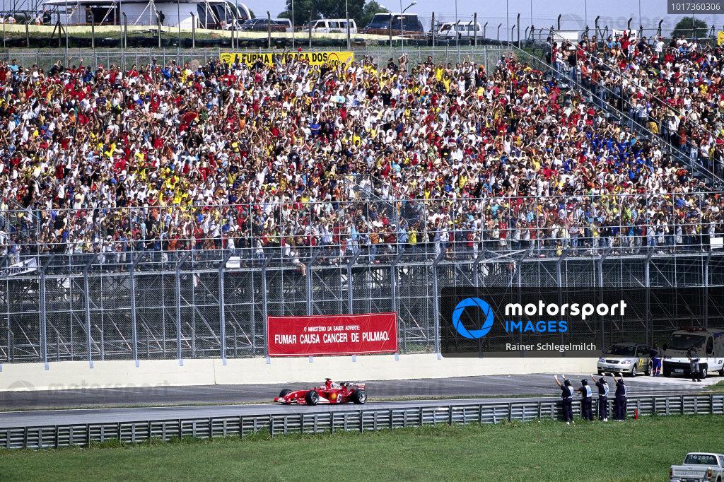 Home driver Rubens Barrichello, Ferrari F2004 passes a cheering grandstand.