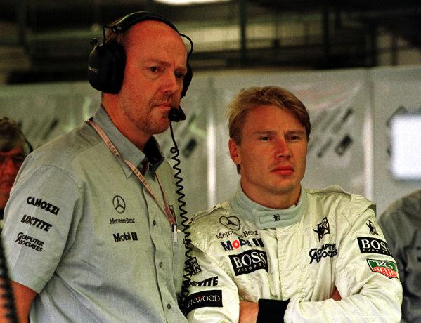 1997 British Grand Prix.Silverstone, England.11-13 July 1997.Mika Hakkinen (McLaren Mercedes-Benz) and engineer Steve Hallam in the garage.World Copyright - LAT Photographic