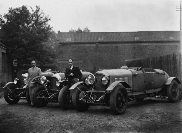 "The Bentley 4-1/2 litre team cars for the 1929 Le Mans race (the lead lined ballast tubes across the tops of the dumb-irons, and the central headlights are the give away). Henry ""Tim"" Birkin on the left and Frank Clement leaning on the wing of the prototype 41/2 in the middle. No hoods had to be erected that year so the newer cars did not have the ""traditional"" squared-off tails which had been used in previous races. The photo could be at Barnato's house ""Ardenrun"" near Lingfield, Surrey, where the team used to stop for lunch before catching the ferry from Newhaven, portrait. World Copyright: LAT Photographic.Ref:  Autocar Glass Plate Red 4485."