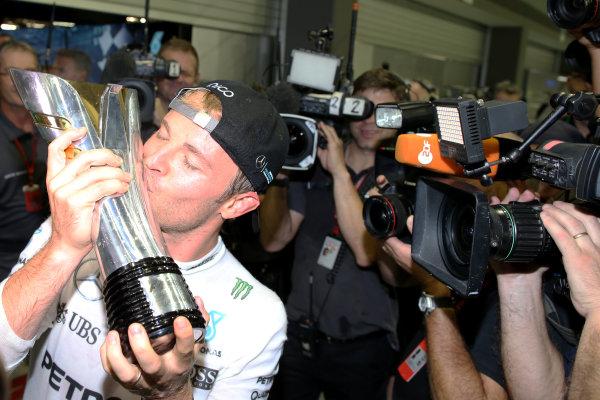 Marina Bay Circuit, Marina Bay, Singapore. Sunday 18 September 2016. Nico Rosberg, Mercedes AMG, 1st Position, kisses his trophy after the podium ceremony. World Copyright: Charles Coates/LAT Photographic ref: Digital Image DJ5R3313