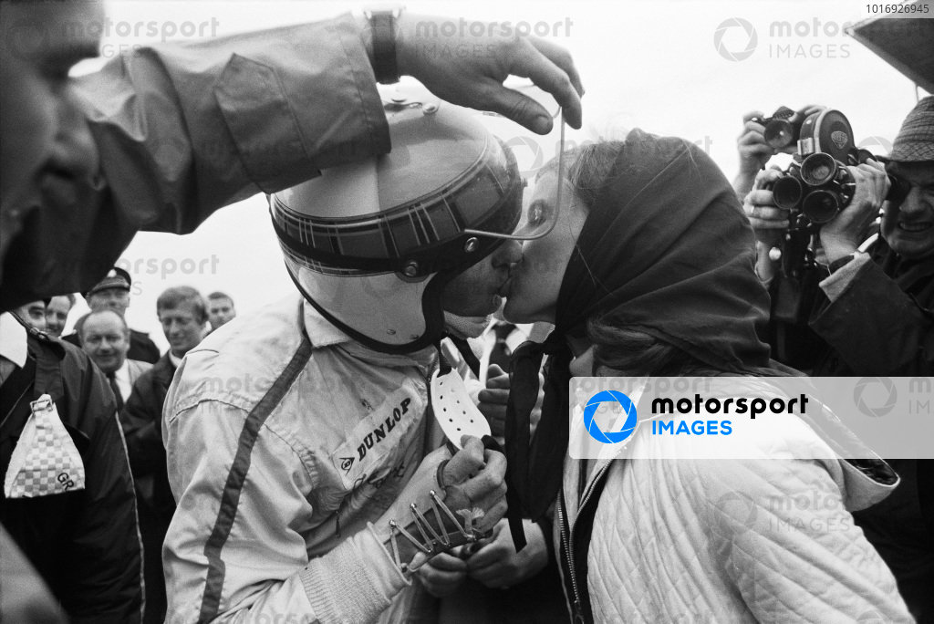 Helen Stewart kisses her husband, Jackie, after his win. Somebody is helpfully holding Jackie's visor up as his broken wrist is in a cast.