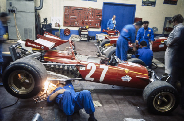 Mechanics work on the Ferrari 312B of Jacky Ickx in the garage.