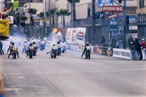 Barry Sheene, Suzuki, Skip Aksland, Yamaha, Gene Romero, Yamaha, and Mike Baldwin, Yamaha, lead the riders away at the start.