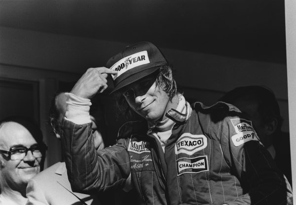 Brands Hatch, England. 16th - 18th July 1976.  James Hunt (McLaren M23 Ford), Disqualified, points to his tyre sponsor on his cap on the podium, portrait.  World Copyright: LAT Photographic.  Ref: 8877 - 19.